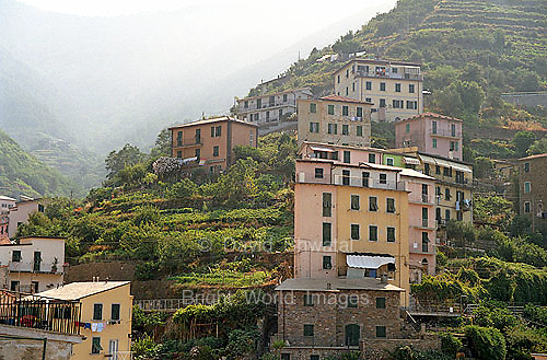 Morning mist lingers in a valley above the Cinque Terre village of Riomaggorie, Italy.