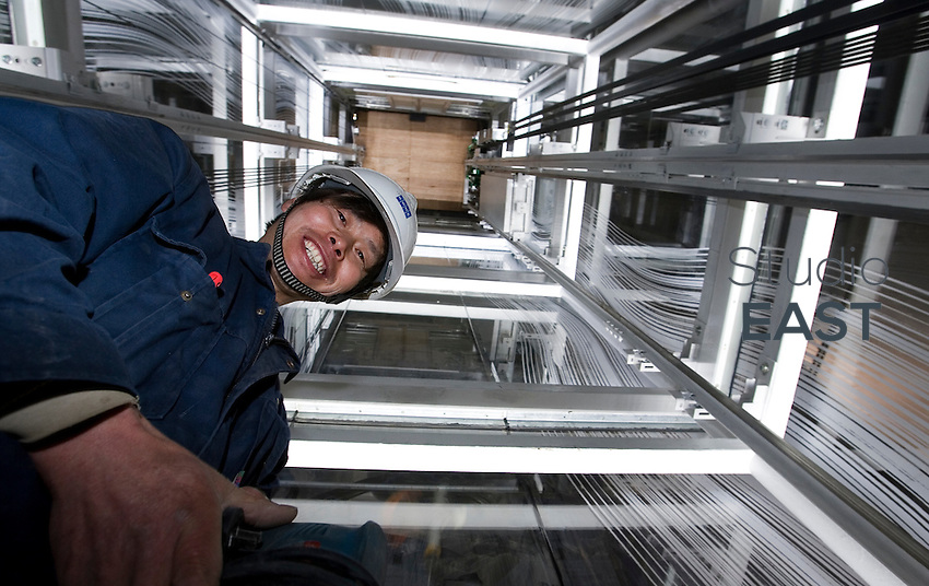 Workers work on the 'Lantern' Kone elevator in the Finnish Pavilion, in Shanghai World Expo 2010 site, China, on April 9, 2010. Photo by Lucas Schifres/Pictobank