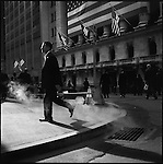 A man passed in front of the New York Stock Exhchange on Wall Street as steam from a street vent was highlighted by the lunchtime sunshine. New York City, New York, November 12, 2008