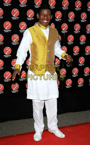 HAILE GEBRSELASSIE.At the Sport Industry Awards, Battersea Evolution, London, England, UK, .May 13th 2010..arrivals full length white shirt  waistcoat gold yellow silk satin tunic trousers    .CAP/CAN.©Can Nguyen/Capital Pictures.