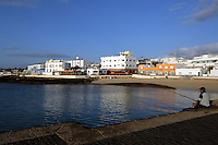 Lone fisherman fishing in harbour, Corralejo, Fuerteventura, Canary Islands, Spain