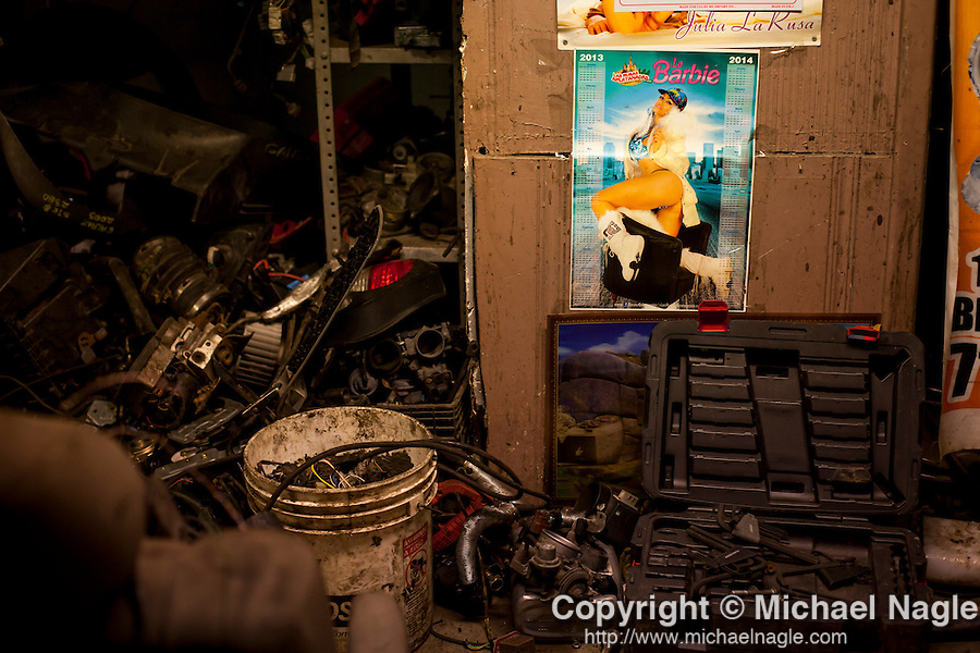 QUEENS, NY -- OCTOBER 25, 2013: Piles of car parts sit next to a pin-up poster in Willets Point on October 25, 2013 in Queens, NY.  PHOTOGRAPH  BY MICHAEL NAGLE FOR THE NEW YORK TIMES