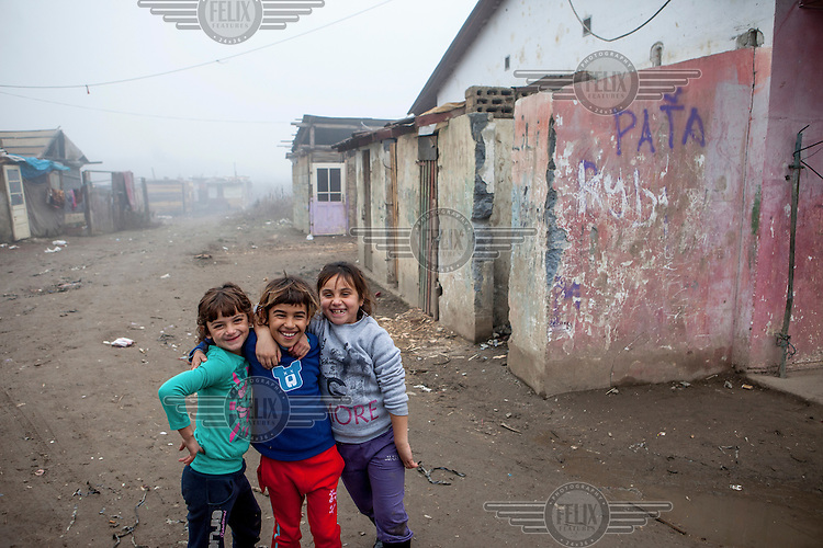 Three young girls laughing together in the Roma settlement located in 'Budulovskej Street'.