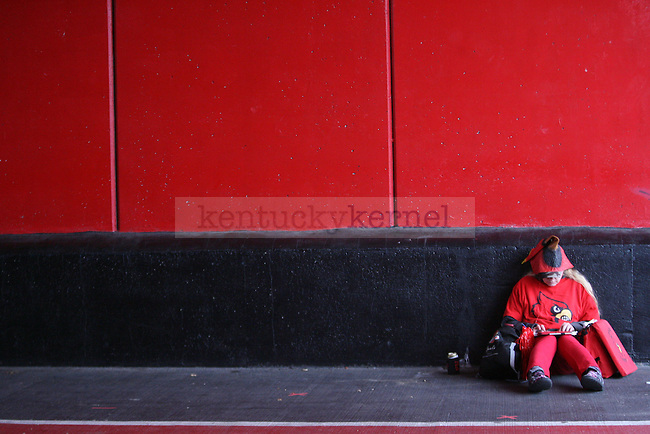 Louisville fan Angela Szalay sits on the ground in the tunnel during the first half of the University of Kentucky vs. University of Louisville at Papa Johns Cardinal Stadium in Louisville, Ky., on Saturday, November 29, 2014. UL won 44 - 40. Photo by Tessa Lighty | Staff