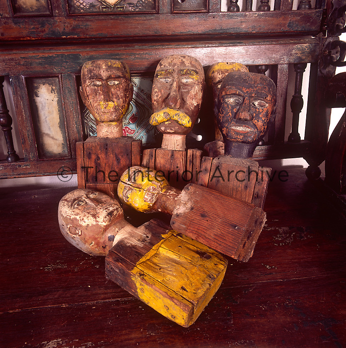 Rough carved wooden heads arranged on a bench seat.