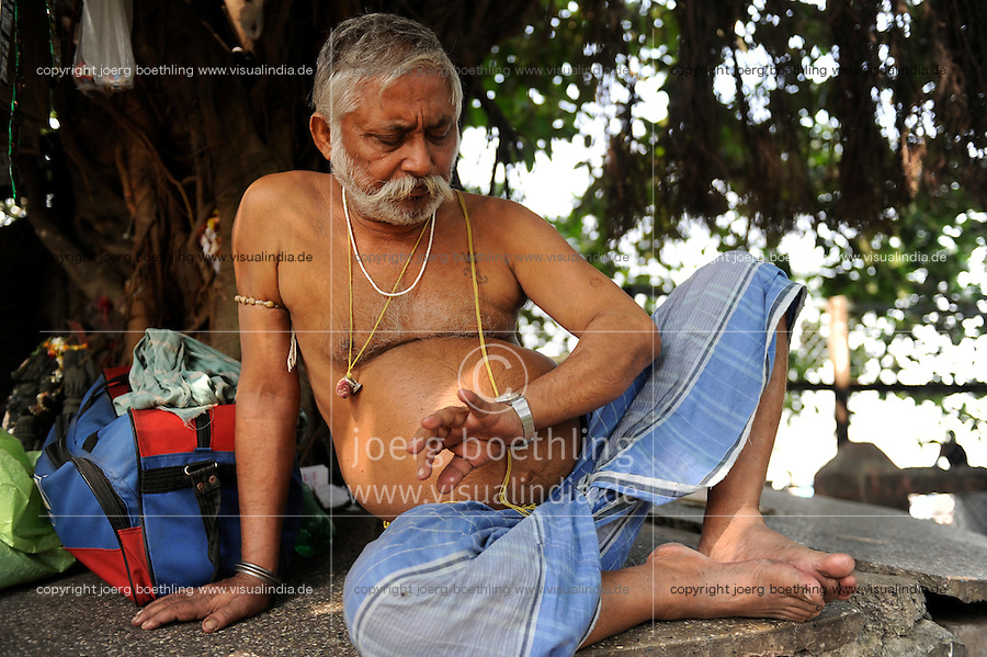 NDIA Kolkata Calcutta, ascet look at watch after sleep under tree at Hooghli river / INDIEN Kolkata , Asket mit dickem Bauch und Lendentuch schaut auf die Uhr nach einem Nickerchen, wie spaet ist es, Zeit zu gehen