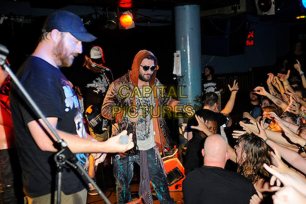 Bam Margera (Brandon Cole 'Bam' Margera)<br /> Fuckface Unstoppable performing in concert, Camden Underworld, London, England. <br /> 23rd July 2013<br /> *special rates apply*<br /> on stage in concert live gig performance performing music half length orange hooded hoody hoodie top sunglasses shades brown velvet jacket beard facial hair fans crowd audience<br /> CAP/MAR<br /> &copy; Martin Harris/Capital Pictures