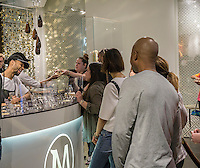 Customers line up for their bespoke Magnum ice cream bar studded with toppings at the Magnum pop-up dipping bar in Soho in New York on Saturday, April 23, 2016. Workers for Magnum, a brand of the Good Humor company, dip your bar in up to three ingredients including everything from Himalayan sea salt to the more plebeian nuts. The pop-up is open through August 7. (© Richard B. Levine)