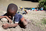 A boy lays in the dirt as women do laundry in the Artibonite River, the source of the recent cholera outbreak, on Sunday, October 31, 2010 in Petite Riviere, Haiti.