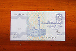 Egyptian 25 Piastres currency note on table with Arabic script and mosque
