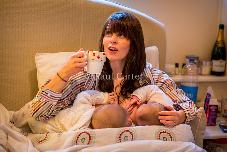 A woman breastfeeding 5 month old twins at the same time on her bed in her bedroom while drinking a cup of tea.<br /> <br /> Image from the &quot;We Do It In Public&quot; documentary photography project collection: <br />  www.breastfeedinginpublic.co.uk<br /> <br /> Hampshire, England, UK<br /> 11/02/2013
