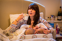 """A woman breastfeeding 5 month old twins at the same time on her bed in her bedroom while drinking a cup of tea.<br /> <br /> Image from the """"We Do It In Public"""" documentary photography project collection: <br />  www.breastfeedinginpublic.co.uk<br /> <br /> Hampshire, England, UK<br /> 11/02/2013"""