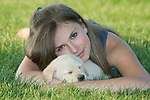 Teenager holding a sleeping Yellow Labrador retriever (AKC) puppy
