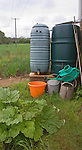 Watering cans and water butts and plastic bucket on allotment garden, UK