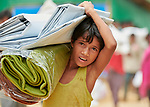 A Rohingya boy carries a tarp and blankets he received during a distribution of aid from several groups, including Dan Church Aid, in the Jamtoli Refugee Camp near Cox's Bazar, Bangladesh. Dan Church Aid is a member of the ACT Alliance.<br /> <br /> More than 600,000 Rohingya have fled government-sanctioned violence in Myanmar for safety in Bangladesh.