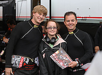 May 3, 2013; Commerce, GA, USA: NHRA top fuel dragster driver Steve Torrence (right) and funny car driver Blake Alexander (left) pose for a picture with a young fan while waiting in a rain delay during qualifying for the Southern Nationals at Atlanta Dragway. Mandatory Credit: Mark J. Rebilas-