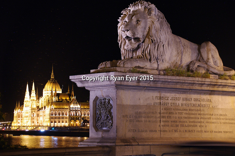 BUDAPEST - 22 July 2015 - The lions guarding the Széchenyi Chain Bridge in Budapest. Completed in 1849,  the Széchenyi Chain Bridge is a suspension bridge that spans the River Danube between Buda and Pest. The lions at each of the abutments were carved in stone by the sculptor, János Marschalkó. In the background, the Buda Castle, also known as the Royal Palace, can be seen. Picture: Ryan Eyer