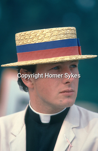 Henely on Thames, regatta week, your vicar wears a straw boater with rowing club colours colors. Oxfordshire UK