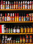 Bottles of hot sauce fill the shelves of a spice shop.