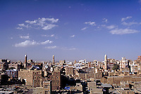 Sana's minaret towers project high above the mud brick buildings. Architecture, religion, mosque, Islam, city, cities,. Sana, Yemen.