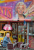 An elderly man sits beneath a picture of Marilyn Monroe advertising an amusement arcade in the Yorkshire seaside resort of Bridlington on Easter Bank Holiday.