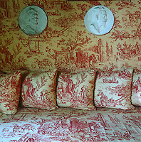 The walls, sofa and a row of scatter cushions are all covered in red and white toile de Jouy in this living room