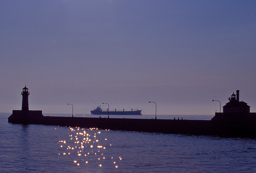 A LARGE FREIGHTER IS SILHOUETTED ON LAKE SUPERIOR BETWEEN THE DULUTH HARBOR NORTH PIER LIGHTHOUSE, LEFT, AND THE DULUTH SOUTH BREAKWATER OUTER LIGHTHOUSE, RIGHT, IN DULUTH, MINNESOTA.