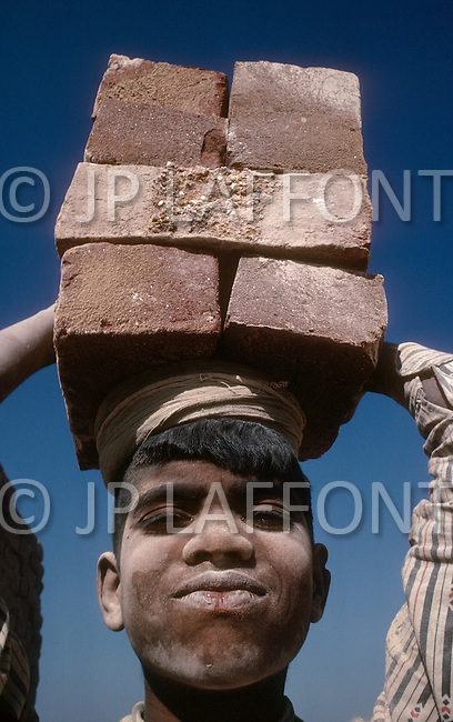 In India, this young boy is employed at a brick-making plant in New Delhi. Child labor as seen around the world between 1979 and 1980 - Photographer Jean Pierre Laffont, touched by the suffering of child workers, chronicled their plight in 12 countries over the course of one year.  Laffont was awarded The World Press Award and Madeline Ross Award among many others for his work.
