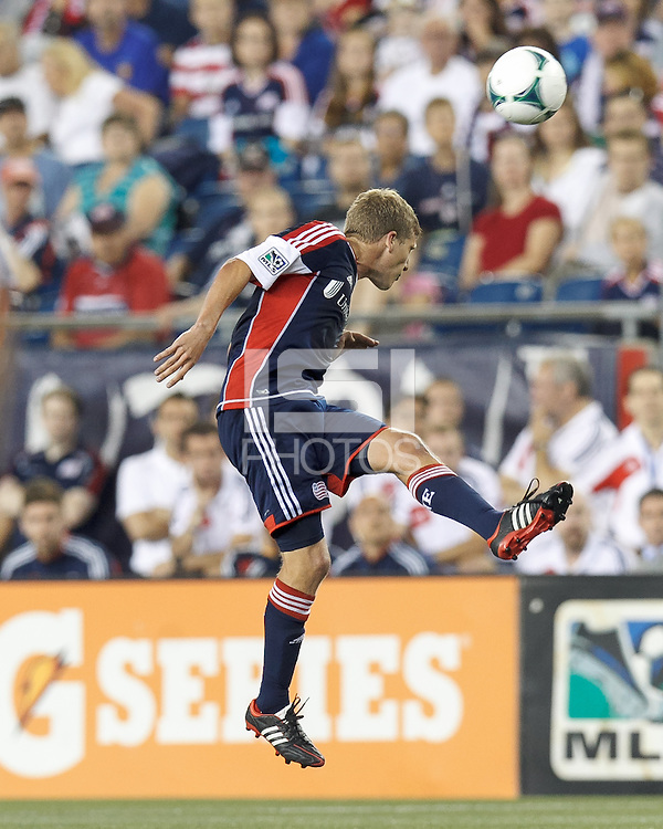 New England Revolution midfielder Scott Caldwell (6) heads the ball. In a Major League Soccer (MLS) match, the New England Revolution (blue) defeated Chicago Fire (red), 2-0, at Gillette Stadium on August 17, 2013.