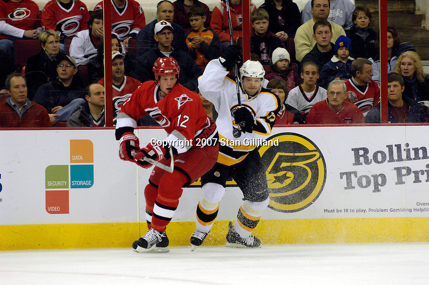 Boston Bruins' Petr Tenkrat (17) and the Carolina Hurricanes' Eric Staal (12) keep their eyes on a floating puck Saturday, Feb. 3, 2007 at the RBC Center in Raleigh. Boston won 4-3 in overtime.