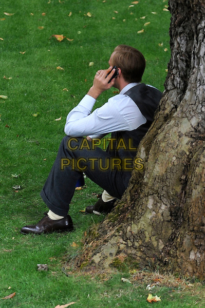 "JAMES D'ARCY .on the set of Madonna's movie ""WE"" in London, England, UK, July 25th 2010. *Exclusive All-Rounder*.full length grey gray waistcoat on set location filmset film trousers costume sitting tree phone talking side back rear behind .CAP/IA.©Ian Allis/Capital Pictures."