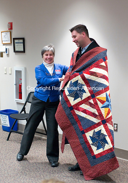 "Cheshire, CT- 24 November 2015-112415CM07- Jane Dougherty, left, Co-coordinator with the Connecticut  Quilts of Valor Foundation, hugs former U.S. Army Captain Justin Nash, who served in Afghanistan, at the Cheshire Library on Tuesday. Dougherty  gave a presentation about the Quilts of Valor Foundation which provides service members and veterans, touched by war with comforting quilts of valor both home and aboard.  Nash founded  ""Til Duty Is Done"" a non-profit, that provides a safe and secure community for veterans through supportive housing, employment training, and employment opportunities.   Christopher Massa Republican-American"