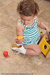 13 month old baby girl at home on floor playing with toy geometric shape sorter looing at shape she holds in her hand vertical