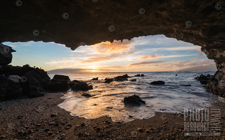 Sunset seen from a hidden cave on the west side of Maui as the ocean washes in.