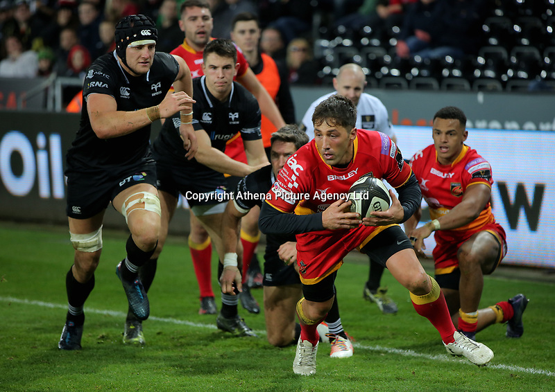 Gavin Henson of the Dragons (R) escapes with the ball during the Guinness PRO14 match between Ospreys and Dragons at The Liberty Stadium, Swansea, Wales, UK. Friday 27 October 2017