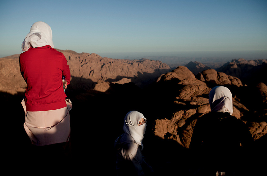 Shortly after sunrise, three young women look out from the summit of Mount Sinai, Egypt, October 2009. Photo: Ed Giles.