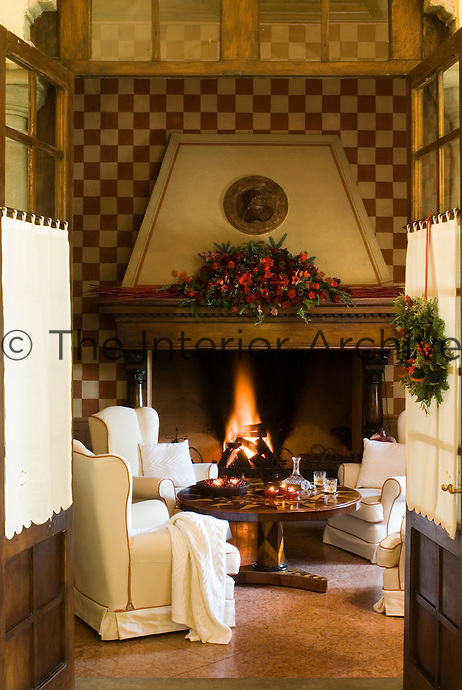 Looking into the cosy living room decorated for Christmas with a festive flower dispaly on the mantelpiece over the roaring fire