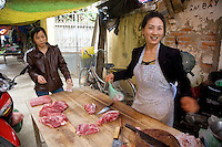 Vietnam. Ha Tay province. Lai Xa. A woman smiles while serving a customer. Butcher's stall at the meat market. Lai Xa is a typical hamlet (village) and is part of the Kim Chung commune located 15 km west of Hanoi. 06.04.09 © 2009 Didier Ruef