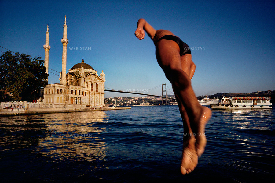 1993. A young man dives in the waters of the Bosphorus with Bosphorus bridge and Ortakay Mosque in the background. Un jeune homme plonge dans les eaux du Bosphore avec le pont du Bosphore et la mosquée Ortakay en arrière-plan.