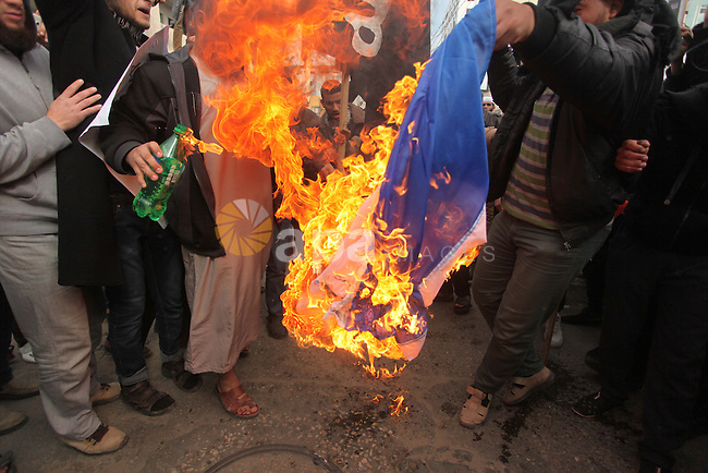 Palestinian Salafists burn a French national flag during a protest against the satirical French weekly magazine Charlie Hebdo's cartoons of the Prophet Mohammad, in Gaza city January 19, 2015. Dozens of Jihadist Salafi men rallied in Gaza on Monday to condemn continued publication by French satirical magazine Charlie Hebdo of cartoons deemed offensive to Islam's Prophet. Charlie Hebdo published a picture of Mohammad weeping on its cover last week after gunmen stormed its offices in Paris, killing 12 people. The gunmen said the attack was revenge for cartoons the magazine had published mocking Islam. Photo by Ashraf Amra