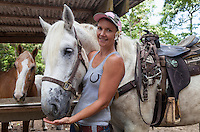 The owner of Na'alapa Stables feeds a white horse; the company offers horseback riding tours in Waipi'o Valley, Big Island.