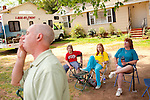 Mark Symms talks to a person across the street, while his nephew Jacob Sale, 11, daughter Baylie Symms, 13, and sister Amy Symms sit in their yard waiting for people to use their lots to park in along Azalea Drive during The Masters Golf Tournament in Augusta, Georgia April 7, 2010. The family has two neighboring lots, which can fit 90 cars, and have sold daily parking spots since 1973.