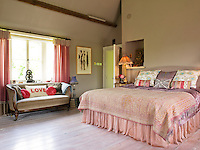 This feminine bedroom is furnished with a velvet-covered sofa and cushions and a generous double bed