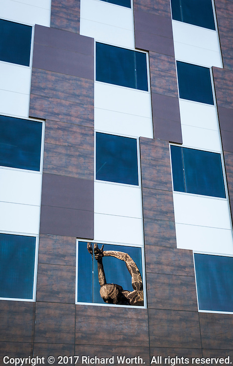 """The raised arms and head of the """"Truth is Beauty"""" sculpture is reflected in a window of the San Leandro Tech Campus."""