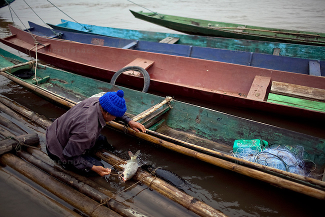 """Mon, 62, has been a fisherman for 10 years on the Mekong River in Sop Ruak, Thailand. He says things were better before China built dams and controlled the water level of the river. """"I used to cast my net and catch 10-12 fish now I some times come back with none,"""" he said. Photo taken on Thursday, December 10, 2009. Kevin German / Luceo Images"""