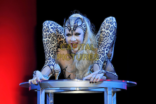 GUEST.Erotica, the world's largest lifestyle show for adults at Olympia Exhibition Centre, London, England. .November 19th, 2010.gv general view atmosphere full length leopard print catsuit contortionist  bending gesture .CAP/MAR.© Martin Harris/Capital Pictures.