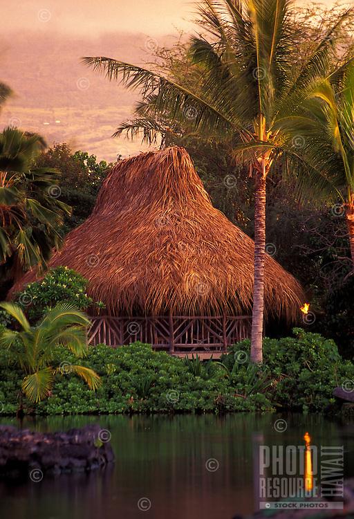 Grass hut with palm tree at Kona village resort on Big island of Hawaii at twighlight
