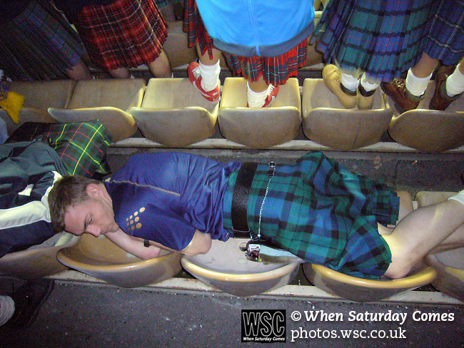Ukraine 2 Scotland 2, 11/10/2006. Olympic Stadium, Euro 2008 Qualifying. A Scotland fan, a member of the Tartan Army, takes a nap in the stand prior to his team's against Ukraine. Ukraine defeated Scotland 2-0 after a goal-less first half in this Euro 2008 group qualifying match played at the Olympic Stadium in Kyiv (Kiev). This was the first competitive international match between the countries. Photo by Colin McPherson.