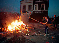The Falls, Belfast, Northern Ireland: Catholic children make a fire in the street during riots.