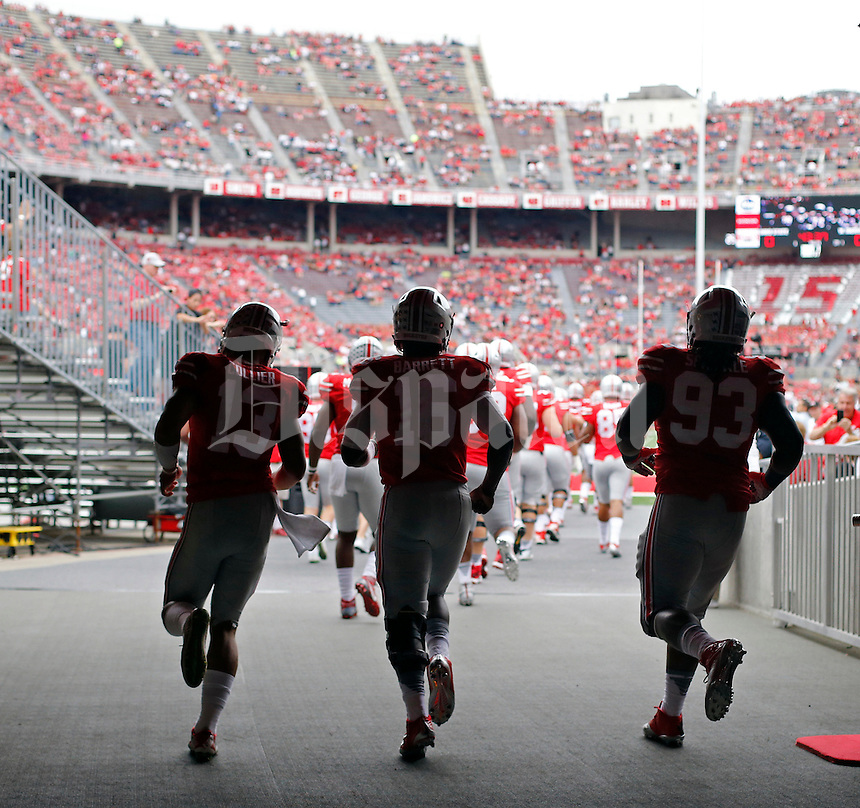 Ohio State Buckeyes quarterback Stephen Collier (13), Ohio State Buckeyes quarterback J.T. Barrett (16) and Ohio State Buckeyes defensive lineman Tracy Sprinkle (93) make their way out for final warmups  before their game against Western Michigan Broncos at Ohio Stadium on September 26, 2015.  (Dispatch photo by Kyle Robertson)